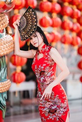 Portrait beautiful smiles Asian young woman wearing red traditional Chinese cheongsam decoration and holding a Chinese Fanning for Chinese New Year Festival at Chinese shrine in Thailand