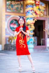 Portrait beautiful smiles Cute little Asian girl wearing red traditional Chinese cheongsam decoration for Chinese New Year Festival at Chinese shrine