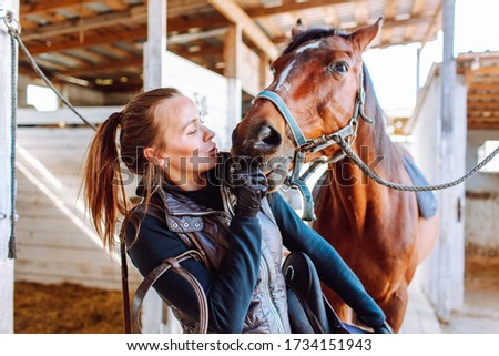 Portrait beautiful smiling woman long hair next to her horse in a stable. Horseback riding