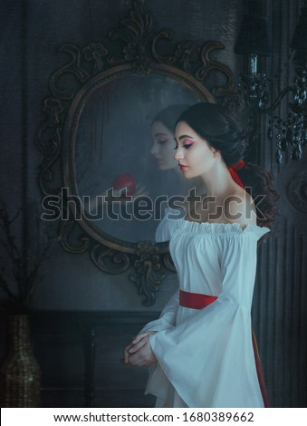 Portrait beautiful woman concept sleeping beauty fairytale Snow White. medieval clothes dress. Gothic princess makeup red lips. Ghost female hand with poison apple is reflected vintage antique mirror