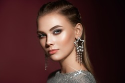 Portrait beautiful woman with jewelry. Brunette girl with long smooth hair. Beauty fashion. Eyelashes. Cosmetic eyeshadow. Care and beauty hair products. Model in a silver dress