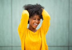 Portrait beautiful young african american woman smiling with hands in hair by green background