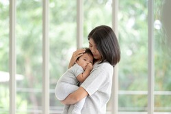 Portrait beautiful young Asian mother holding and hugging her newborn baby in living room. Healthcare and Happiness love asia woman lifestyle mother's day concept with copy space.