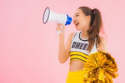 Portrait beautiful young asian woman cheerleader with megaphone on pink isolated background