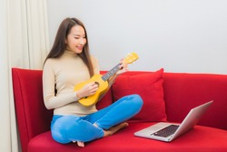 Portrait beautiful young asian woman play ukulele on sofa in living room interior