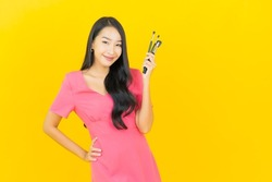 Portrait beautiful young asian woman smile with cosmetic make up brush on yellow color background