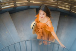 Portrait beautiful young asian woman walk on circle stair with smile and happy