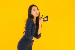 Portrait beautiful young asian woman with makeup brush on yellow isolated background