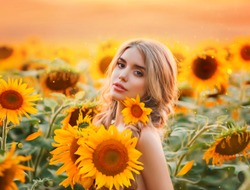 portrait beautiful young blonde woman hugs bouquet yellow flowers. Cute pretty face fairy tale princess. background bright field blooming sunflowers. Artwork photo fantasy fiery sunset summer nature
