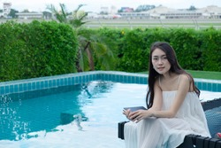 Portrait beautiful youngwomen  Asian reading a book on bed chair around the outdoor swimming pool.