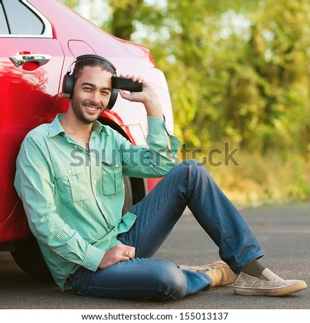 Portrait boy listening to mp3 player outdoors