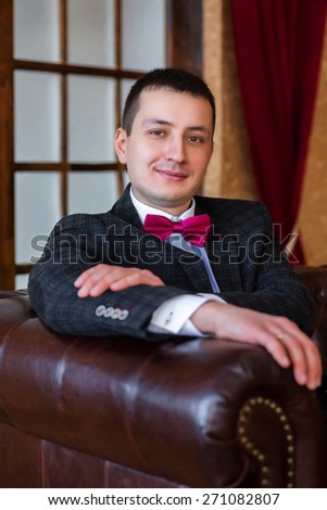Portrait bridegroom sitting in a leather chair