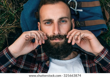 Portrait brutal bearded hipster man in the forest