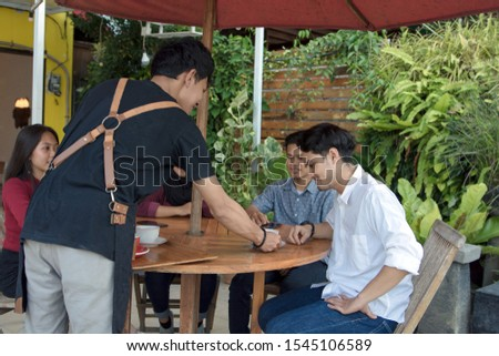 portrait cafe waitress serving guests who sitting in a garden-decorated cafe by delivering drinks with trays #1545106589