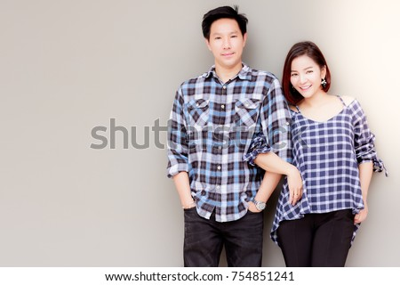 Portrait charming couple: An attractive young woman walks arm in arm her boyfriend or middle aged man. They feel so relaxed and happy. They're in love each other for long time with copy space.
