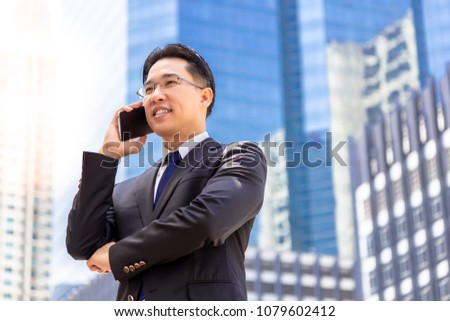 Portrait charming handsome executive man: Attractive businessman or boss is calling his customer for asking deal of business. Handsome middle aged man get satisfied agreement of deal. city background