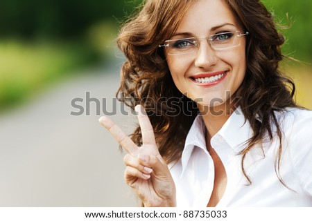 stock photo : portrait charming young gay woman glasses shows sign victory ...