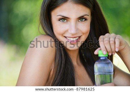 portrait charming young long-haired bare woman holding bottle water background green park