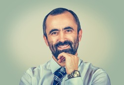 Portrait cheerful bearded man with hand on chin looking to you camera isolated on light green yellow background. Successful entrepreneur. Contented boss with white modern chemise, tie and watch.