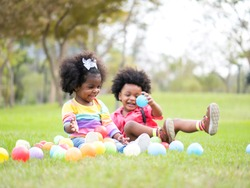 Portrait children Afican American happily playing colorful balls in a park.