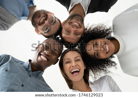 Portrait close up bottom view happy faces of diverse employees team standing in circle, looking at camera, smiling businesswomen and businessmen engaged in team building, posing for photo