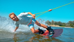 PORTRAIT, CLOSE UP Cheerful young surfer wakeboarding, sliding his hand on water surface, splashing water at camera. Smiling wakesurfer riding waterski cable park on sunny day. Wakesurfing in summer