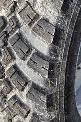 Portrait close up of a muddy grimy tractor rubber tire wheel pattern