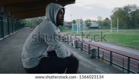 Portrait close up of young african male athlete is taking a break after training in athletics stadium.