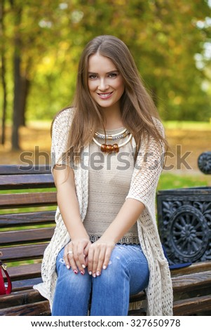 Portrait close up of young beautiful blonde woman sitting on bench, on background autumn park #327650978