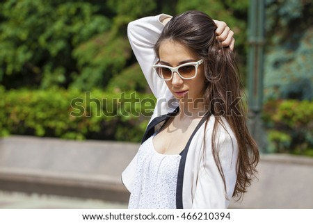 Portrait close up of young beautiful brunette woman in white fashion sunglasses, summer street outdoors #466210394