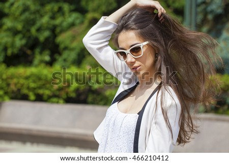 Portrait close up of young beautiful brunette woman in white fashion sunglasses, summer street outdoors #466210412