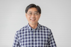Portrait close up shot of middle aged asian male model with short black hair wearing blue plaid shirt with stand smiling in front of white background.