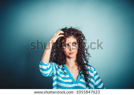 Portrait closeup funny confused skeptical woman girl female thinking with memory loss looking up isolated blue wall background copy space above head. Human expressions emotions feelings body language