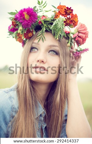 Portrait closeup of beautiful young woman wearing flower crown having fun relaxing looking up on summer green outdoors copy space background