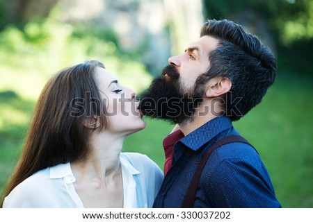 Portrait closeup view of beautiful funny young pair of woman biting man with long lush black beard standing sunny day outdoor on green grass on natural backdrop, horizontal photo