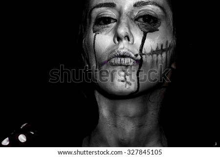 Portrait closeup view of one halloween holiday celebration character young woman with spooky painted face of zombi looking forward black and white, horizontal picture