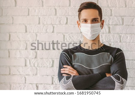 Portrait confident sports man with crossed arms in medical face mask. Personal protection against COVID-19. Young professional fitness trainer in protective mask on face. Coronavirus home quarantine
