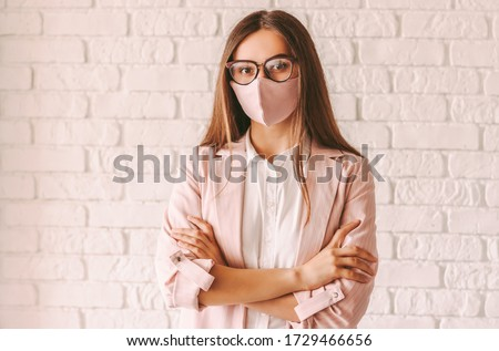 Portrait confident young female entrepreneur in protective face mask, suit and eyeglasses keep arms crossed. Beautiful professional business woman in glasses wearing pink medical face mask. Girl boss