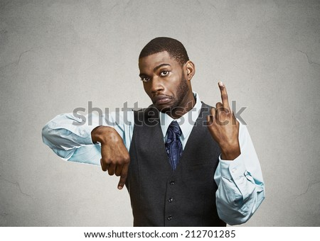 Portrait confused young business man pointing in two different directions, not sure which way to go in life, hesitant to make decision isolated grey background. Emotion facial expression body language
