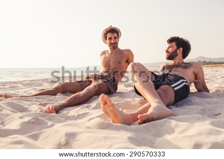 Portrait. Couple of male friends at sunset on the beach on a day of rest summer vacation together, after spending a day of relaxation and fun.