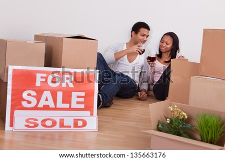 Portrait Couple Sitting Among Moving Boxes Making Celebration In House