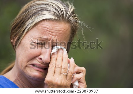 Portrait crying mature woman in grief, with sad unhappy, stressed emotional facial expression, suffering painful depression, tissue in hands, outdoor blurred background.