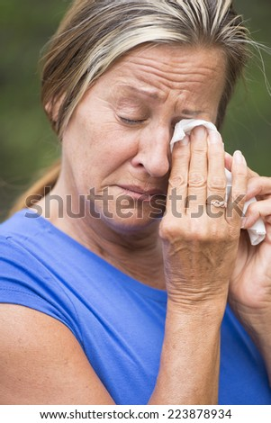 Portrait crying mature woman with sad unhappy emotional facial expression, in grief or suffering painful depression, with tissue in hands, outdoor blurred background.