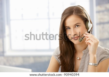 Portrait customer service operator girl wearing headset, smiling at camera, copyspace.?