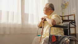Portrait depressed lonely elderly man with wooden cane looking at windows, frustrated mature male folded hands on walking stick, sitting on wheelchair alone, loneliness and solitude, Care, Retirement.