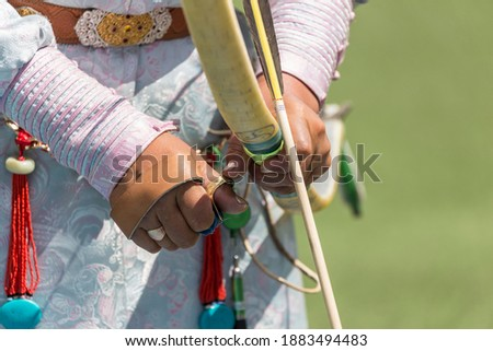 Portrait detail with selective focus on the manicured hand and rings and strapping of a Mongolian lady archer holding a bow at the archery competition at the Naadam Festival in Ulan Bator in Mongolia Stock fotó ©
