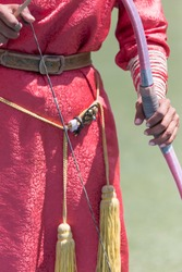 Portrait detail with selective focus on the manicured hand of a Mongolian lady archer holding a pink archery bow at the archery competition at the famous Naadam Festival in Ulaanbaatar in Mongolia