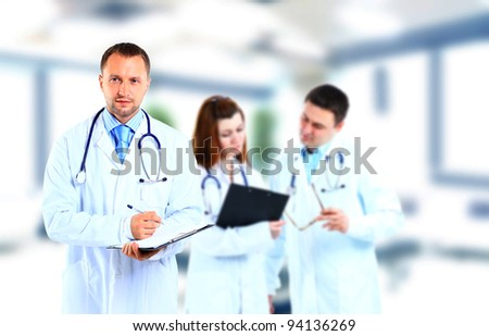 Portrait doctor smiling with colleagues in background