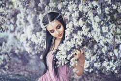 Portrait elf pretty cute woman in blooming garden. long ears. touches white flowers spring tree. purple luxury dress pearls. Art photography. Perfect skin tender makeup, smiling face. Tiara diadem