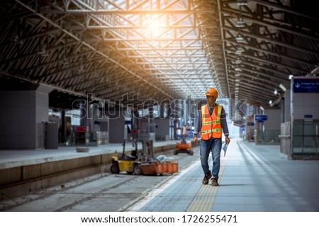 Portrait engineer under inspection and checking construction process railway and checking work on railroad station .Engineer wearing safety uniform and safety helmet in work.